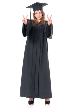 Beautiful graduate girl student in mantle showing victory sign, isolated on white background Stock Photo