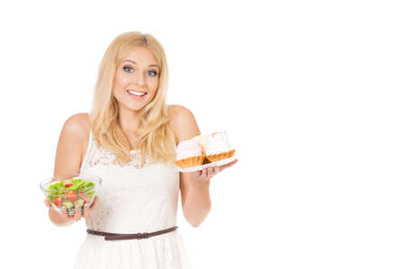 Half-length portrait of very beautiful woman holding small cake, fresh vegetables. Young housewife choosing sweets or healthy eating - cake and salad. Isolated on white background.