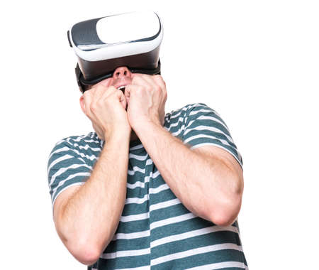 Amazed man wearing virtual reality goggles watching movies, isolated on white background. Surprised male worried and scared making face looking in VR glasses, much gesticulating hands.