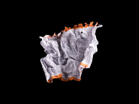 unfolding: Crumpled piece of white blank squared paper exercise book on black background.