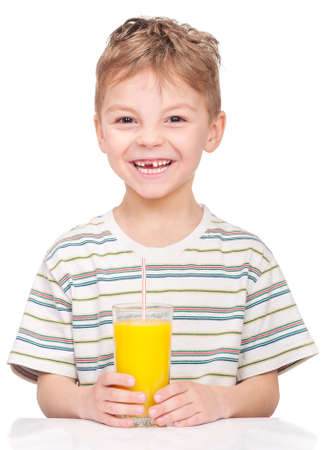 Portrait of happy little boy drinking refreshing orange juice. Smiling child with glass of fresh lemonade. photo