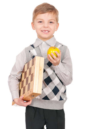 Emotional portrait of caucasian little boy with chessboard and apple. Funny child holding a game of chess in his arms while laughing. Cute smart kid, isolated on white background. photo