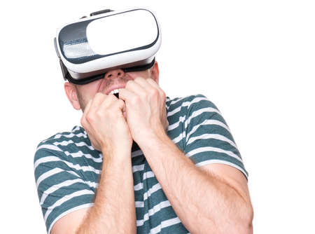 Young man with a frightened pose with virtual reality goggles watching movies or playing video games, isolated on white background. Man is looking scared. People experiencing 3D gadget technology. photo