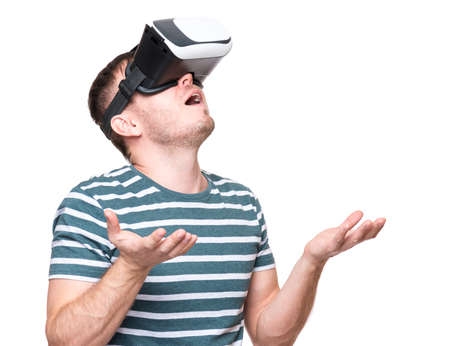 Amazed handsome man wearing virtual reality goggles watching movies or playing video games gesticulating hands. Surprised male looking in VR glasses. People experiencing 3D gadget technology. photo