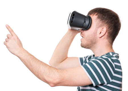 Amazed man wearing virtual reality goggles watching movies or playing video games, isolated on white background. Surprised male in VR glasses. People experiencing 3D technology. photo