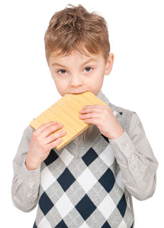 Portrait of happy little boy eating waffle isolated on white background. Child looking at camera. photo
