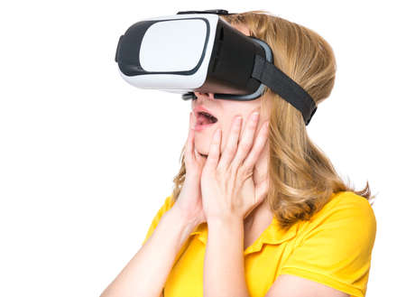 virtual reality simulator: Amazed woman wearing virtual reality goggles watching movies or playing video games, isolated on white background. Surprised girl looking in VR glasses. People experiencing 3D gadget technology.
