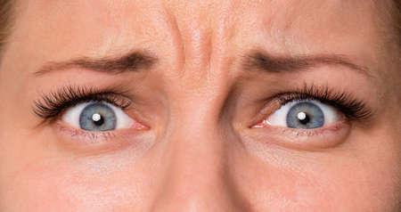 Primer plano rostro asustado de hermosa mujer joven con hermosos ojos azules y grandes pestañas y cejas bonitas. Macro de ojos humanos: sorpresa o conmoción, mirando a la cámara. Foto de archivo