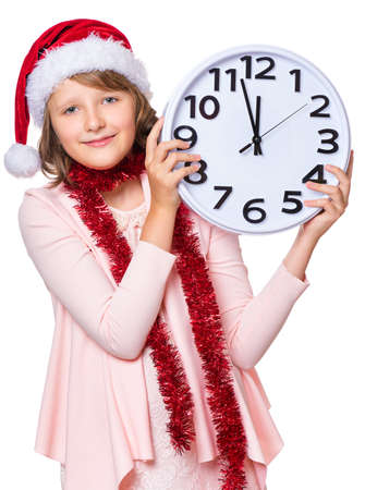 Portrait of smiling little girl with Santa Claus hat. Holiday Christmas concept - happy cute child holding big clock, isolated on white background.