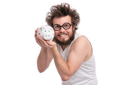 Crazy bearded Man with funny Haircut in eye Glasses holding Piggy Bank, isolated on white background. Saving Money concept. Male gently hugs his piggybank. Archivio Fotografico