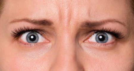 Nahaufnahme trauriges Gesicht der schönen jungen Frau mit schönen blauen oder grauen Augen und großen hübschen Wimpern und Augenbrauen. Makro menschlicher Augen - unglücklich oder verängstigt, Blick in die Kamera. Standard-Bild