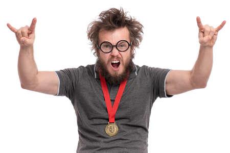 Gelukkige winnaar. Crazy bebaarde Man in bril viert zijn succes. Vrolijke man met gouden medaille, schreeuwen en het maken van rock-'n-roll teken, geïsoleerd op een witte achtergrond.
