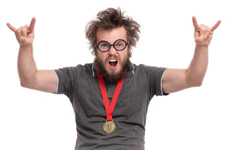Happy winner. Crazy bearded Man in eye Glasses celebrating his success. Cheerful Guy with gold Medal, screaming and making rock and roll sign, isolated on white background.