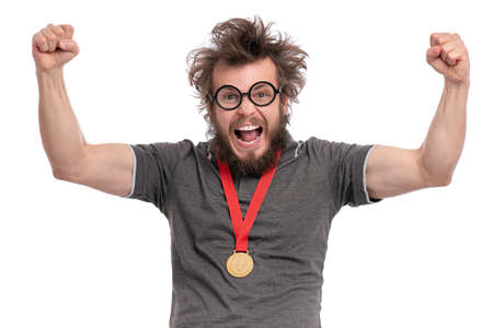 Happy winner. Crazy bearded Man with funny Haircut in eye Glasses celebrating his success. Cheerful Guy with gold Medal, screaming and keeping mouth open, isolated on white background. Banco de Imagens