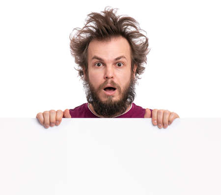 Crazy bearded Man with funny Haircut showing empty blank signboard with copy space. Guy with surprised eyes and mouth open peeking out from behind big white banner, isolated on white background. Archivio Fotografico