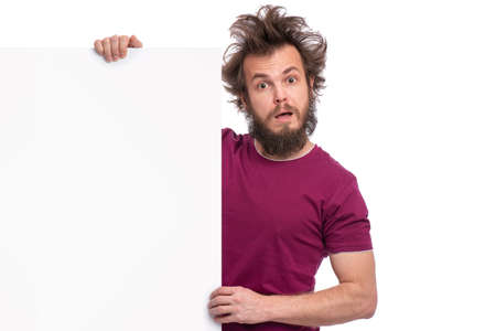 Crazy bearded Man with funny Haircut showing empty blank signboard with copy space. Guy with surprised eyes and mouth open peeking out from behind big white banner, isolated on white background. Foto de archivo