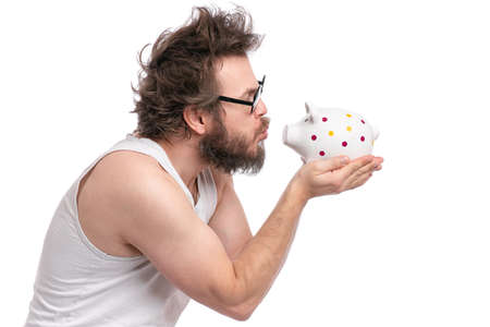 Crazy bearded Man with funny Haircut in eye Glasses holding Piggy Bank, isolated on white background. Saving Money concept. Male carefully kisses his piggy bank.