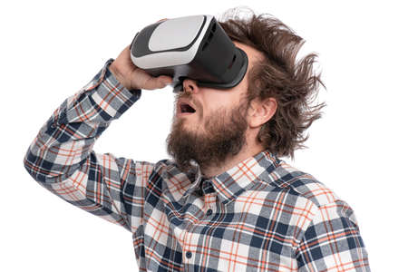 Crazy bearded Man in plaid shirt with funny Haircut wearing virtual reality helmet, isolated on white background. Portrait of funny man using VR goggles. Stock fotó