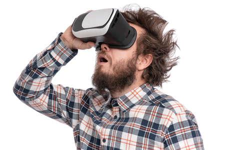 Hombre barbudo loco en camisa a cuadros con corte de pelo divertido con casco de realidad virtual, aislado sobre fondo blanco. Retrato de hombre divertido con gafas de realidad virtual. Foto de archivo
