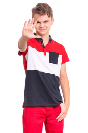 Teen boy doing stop sign with palm of hand, isolated on white background. Beautiful caucasian teenager making stop gesture with negative and serious facial expression. Angry child looking at camera.