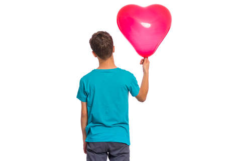 Back view. Portrait of teen boy holds red heart shaped balloon, isolated on white background.
