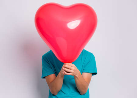 Teen boy hiding behind red heart shaped balloon. Child holding symbol of love, family, hope. Celebration of Saint Valentines Day. Teenager cover face posing in studio.