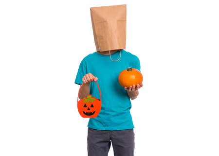 Happy halloween concept. Teen boy with paper bag over his head holds orange pumpkin bucket and small pumpkin, isolated on white background. Teenager cover head with bag. Child waiting candy. Foto de archivo