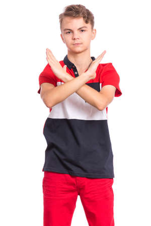 Portrait of teen boy doing stop sign with crossed hands, isolated on white background. Cute caucasian young teenager making stop gesture with serious facial expression. Child looking at camera.