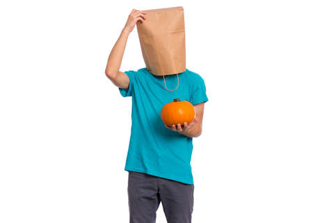 Happy halloween concept. Teen boy with paper bag over his head holds orange small fresh pumpkin, isolated on white background. Teenager cover head with bag. Child with food - raw vegetables in hands.