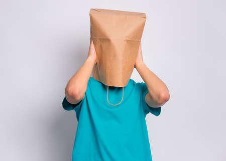 Portrait d'un adolescent avec un sac en papier sur la tête couvrant les oreilles avec ses mains. Tête de couverture d'adolescent avec sac fermant les oreilles avec des paumes posant en studio. Enfant tirant un sac sur la tête. N'entendez aucun concept diabolique. Banque d'images