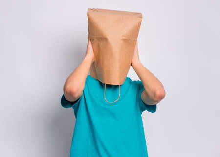 Portrait of teen boy with paper bag over head covering ears with his hands. Teenager cover head with bag closing ears with palms posing in studio. Child pulling bag over head. Hear no evil concept. Stock Photo