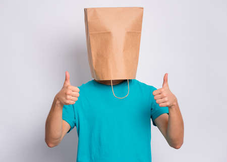 Portrait of teen boy with paper bag over head making thumb up gesture. Teenager cover head with bag showing success sign posing in studio. Child pulling paper bag over head. Imagens