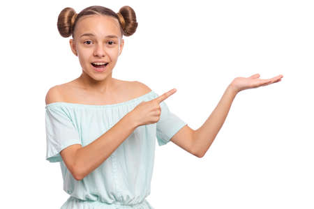 Portrait of teen girl pointing hands away at copyspace, isolated on white background. Beautiful caucasian young teenager smiling and attracted by attention pointing finger at something. Happy child.