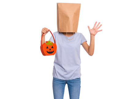 Happy halloween concept. Teen girl with paper bag over her head holds orange pumpkin bucket, isolated on white background. Portrait of teenager cover head with bag. Child waiting candy.