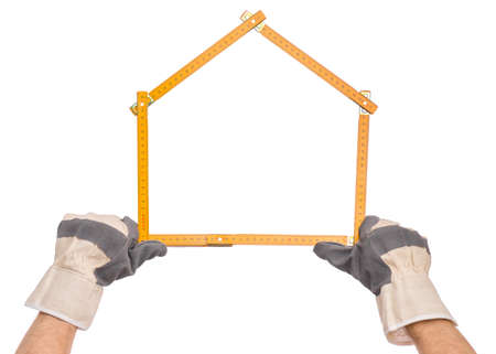 Male Hand wearing Working Glove with yellow wooden meter. Human Hand holding tool forming a house, Isolated on White Background.
