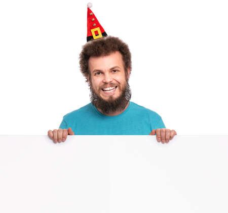 Crazy bearded Man with funny Curly Hair in Christmas hat showing empty blank signboard with copy space. Happy guy in Santa hat peeking out from behind big white banner, isolated on white background.