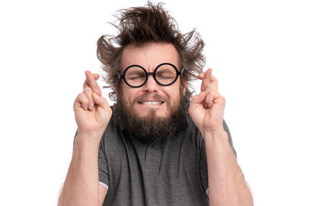 Crazy Bearded happy Man with funny Haircut in Eyeglasses making Luck gesture. Cheerful and silly guy crossing his fingers, isolated on white background.