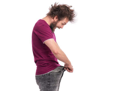 Crazy bearded Man with funny Haircut shows his weight loss by wearing an old jeans, isolated on white background. Surprised or shocked guy. Healthy Dieting or workouts concept.