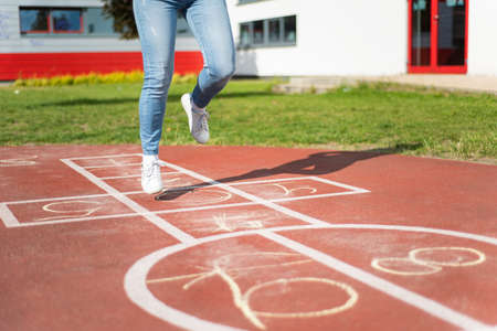 Girl Jumping while Playing Hopscotch at park. Close-up of little cute Girls on Children Playground outdoors. Legs of Kids Jumps Hopscotch on asphalt. Stockfoto