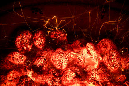 Flame and Fire Sparks at Night. BBQ Grill Pit With Glowing And Flaming Hot Charcoal Briquettes. Cooking Barbecue outdoor.