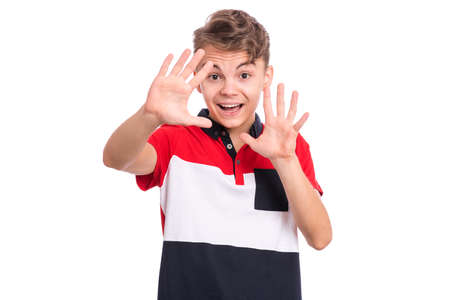 Portrait of surprised teen boy, isolated on white background. Funny child looking at camera in shock or amazement. Handsome caucasian young teenager doing stop sign with palm of hands.