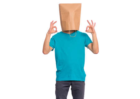 Portrait of teen boy with paper bag over head making Ok gesture, isolated on white background. Child showing okay sign.