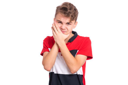 Portrait of teen boy touching his face suffering toothache looking tired and sad. Dental problem. Unhappy beautiful caucasian young teenager suffering from tooth pain, isolated on white background.