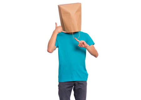 Portrait of teen boy with paper bag over head gesturing with fingers call me, isolated on white background. Child posing in studio showing sign with hand shaped like phone.
