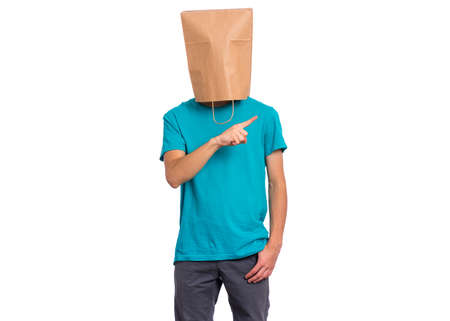 Portrait of teen boy with paper bag over head pointing hands away at copyspace, isolated on white background. Child pointing finger at something.