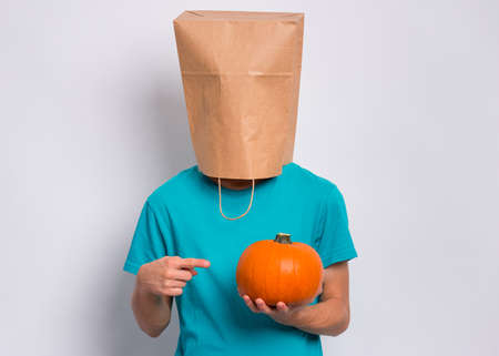 Happy halloween concept. Teen boy with paper bag over his head holds orange small fresh pumpkin, on grey background in studio. Teenager cover head with bag. Child with food - raw vegetables in hands.