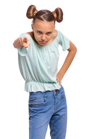 Aggressive angry Teen girl pointing finger on camera, isolated on white background. Emotional portrait of cute caucasian child looking at camera choosing you - accusing someone.