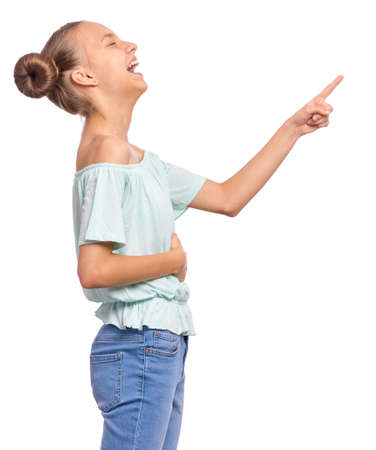 Excited teen girl pointing fingers away at copyspace - side view, isolated on white background. Cute teenager smiling and laughing pointing fingers at something. Happy child looking away - profile.
