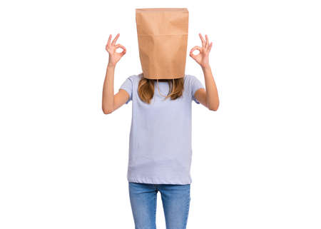 Portrait of teen girl with paper bag over head making Ok gesture. Teenager cover head with bag showing okay sign isolated on white background. Child pulling paper bag over head.