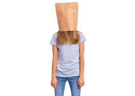 Porträt des jugendlich Mädchens mit Papiertüte über ihrem Kopf, lokalisiert auf weißem Hintergrund. Schüchternes Kind, das Papiertüte über ihren Kopf zieht Teenager bedecken den Kopf mit der Tasche, die im Studio aufwirft. Standard-Bild